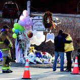 Mourners react after placeing flowers on a memorial built around the sign for the Sandy Hook School in Newtown Saturday, Dec. 15, 2012. Sandy Hook Elementary School was the site of a mass shooting on Friday.