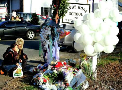 Nicole and Mark Jones, of Danbury, place flowers on a memorial built around the sign for the Sandy Hook School in Newtown Saturday, Dec. 15, 2012. Sandy Hook Elementary School was the site of a mass shooting on Friday, one of the victims was their cousin's daughter. Photo: Michael Duffy