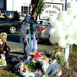 Nicole and Mark Jones, of Danbury, place flowers on a memorial built around the sign for the Sandy Hook School in Newtown Saturday, Dec. 15, 2012. Sandy Hook Elementary School was the site of a mass shooting on Friday, one of the victims was their cousin's daughter.