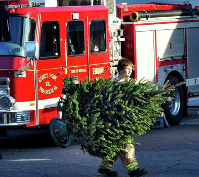 Members of the Sandy Hook Volunteer Fire Department place Christmas trees along Dickenson Drive leading to the Sandy Hook Elementary School in Newtown Saturday, Dec. 15, 2012. The school was the site of a mass shooting on Friday. Photo: Michael Duffy