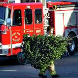 Members of the Sandy Hook Volunteer Fire Department place Christmas trees along Dickenson Drive leading to the Sandy Hook Elementary School in Newtown Saturday, Dec. 15, 2012. The school was the site of a mass shooting on Friday.