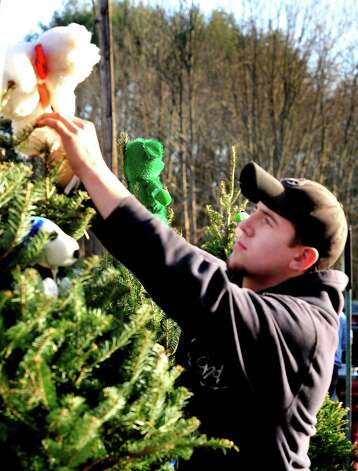 Members of the Sandy Hook Volunteer Fire Department decorate Christmas trees along Dickenson Drive leading to the Sandy Hook Elementary School in Newtown Saturday, Dec. 15, 2012. The school was the site of a mass shooting on Friday. Photo: Michael Duffy