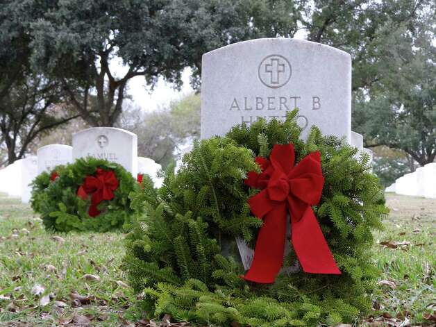 Volunteers placed 9,910 evergreen wreaths at Fort Sam cemetery, adorning nearly a tenth of the 100,000-plus headstones. Photo: Billy Calzada, Express-News / SAN ANTONIO EXPRESS-NEWS