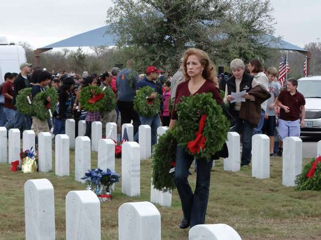Miriam Madden carries wreaths to placed on headstones at Fort Sam Houston during the Wreaths Across America event on Saturday, Dec. 15, 2012. The grave of her husband of 26 years, retired Army Maj. Gary Madden, who died in 2011, received one of the wreaths. They have a son serving in Afghanistan. Photo: Billy Calzada, Express-News / SAN ANTONIO EXPRESS-NEWS