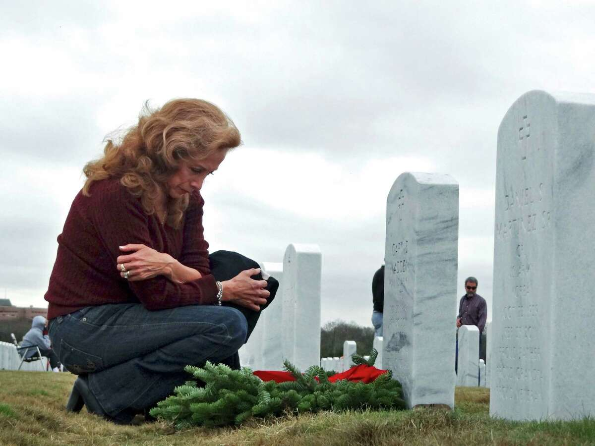 Miriam Madden visits and places a wreath on the grave of her husband of 26 years, retired Army Maj. Gary Madden, who died in 2011, during the Wreaths Across America event at Fort Sam Houston National Cemetery on Saturday, Dec. 15, 2012. Almost 10,000 wreaths were placed among the cemetery's more than 100,000 headstones. They have a son serving in Afghanistan.