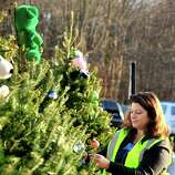 Members of the Sandy Hook Volunteer Fire Department decorate Christmas trees along Dickenson Drive leading to the Sandy Hook Elementary School in Newtown Saturday, Dec. 15, 2012. The school was the site of a mass shooting on Friday.