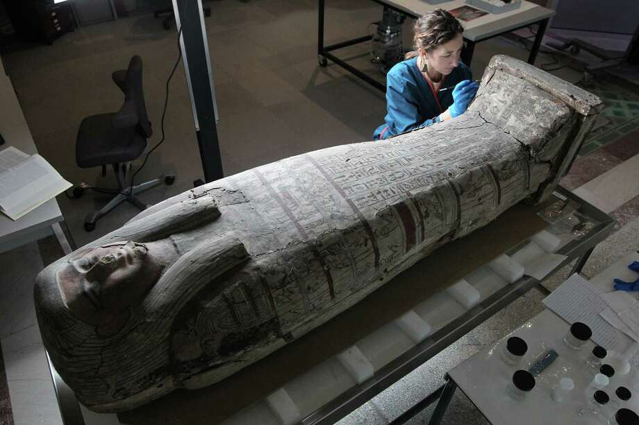 Molly Gleeson uses a brush to clean the exterior of a more than 2,000-year-old Egyptian casket at University of Pennsylvania Museum of Archaeology and Anthropology in Philadelphia. Photo: MICHAEL BRYANT, MBR / Philadelphia Inquirer