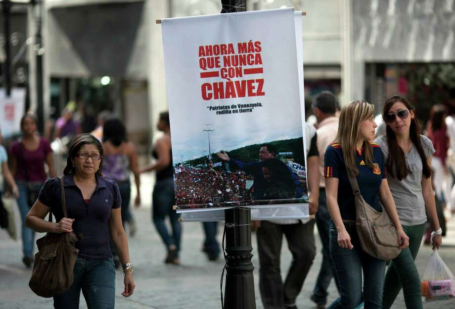 """A banner that reads in Spanish """"Now more than ever with Chavez"""" on a street pole in Caracas, Venezuela, Saturday, Dec. 15, 2012. Hugo Chavez's cancer has upended politics in Venezuela, transforming Sunday's nationwide elections for state governors and legislators into a test of his legacy that could chart the country's future in the uncertain months ahead. (AP Photo/Ariana Cubillos) Photo: Ariana Cubillos"""