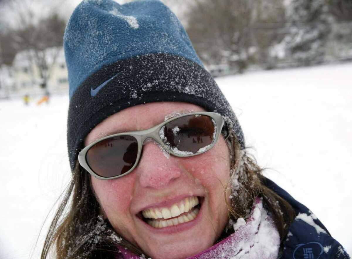 A snow faced Sandy farber smiles after sledding down the hill at Sturges Park in fairfield with her son Devyn, 3, Sunday, Dec. 20, 2009.