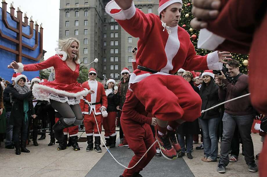 Patrick Lynch (right) and fellow Clauses skip rope in their costumes as the annual SantaCon kicks off at Union Square before spreading to bars around San Francisco. Photo: Michael Macor, The Chronicle