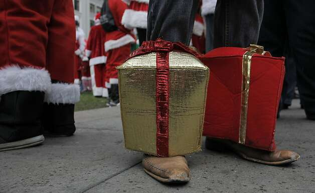 Cowboy boots and presents decorate a party goer as the annual Santacon event kicks off at Union Square and then turns to pub crawls around the city on Saturday Dec. 15, 2012 in San Francisco, Calif. Photo: Michael Macor, The Chronicle