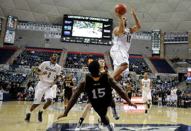 Connecticut's R.J. Evans (12) goes up for a basket as American International College's D.J. Gutridge (15) falls to the court during the first half of a men's NCAA basketball game in Storrs, Conn., Thursday, Nov. 1, 2012. (AP Photo/Jessica Hill) Photo: Jessica Hill, Associated Press / FR125654 AP