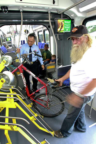 Michael Barrington racks up his bike inside as articulated buses roll out of the new VIA transit station in the South Texas Medical Center on December 15, 2012. Photo: Tom Reel, San Antonio Express-News / ©2012 San Antono Express-News
