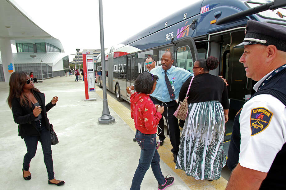 VIA bus driver Alvin Wiliams (center)  welcomes passengers while supervisor Alfred Mendoza watches  as articulated buses roll out of the new VIA transit station in the South Texas Medical Center on December 15, 2012. Photo: Tom Reel, San Antonio Express-News / �2012 San Antono Express-News