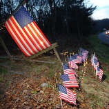 Homeowner Paul Sullivan set up 27 little US flags and lights around a larger flag in memory of the victims from yesterday's mass shooting at Sandy Hook Elementary School, at the edge of his property along I84 in Newtown, Conn. on Saturday December 2012. The larger flag was put up back on 9/11 and was replaced every other year or so. Sullivan thought it would be fitting to add the little flags because of the tragedy.