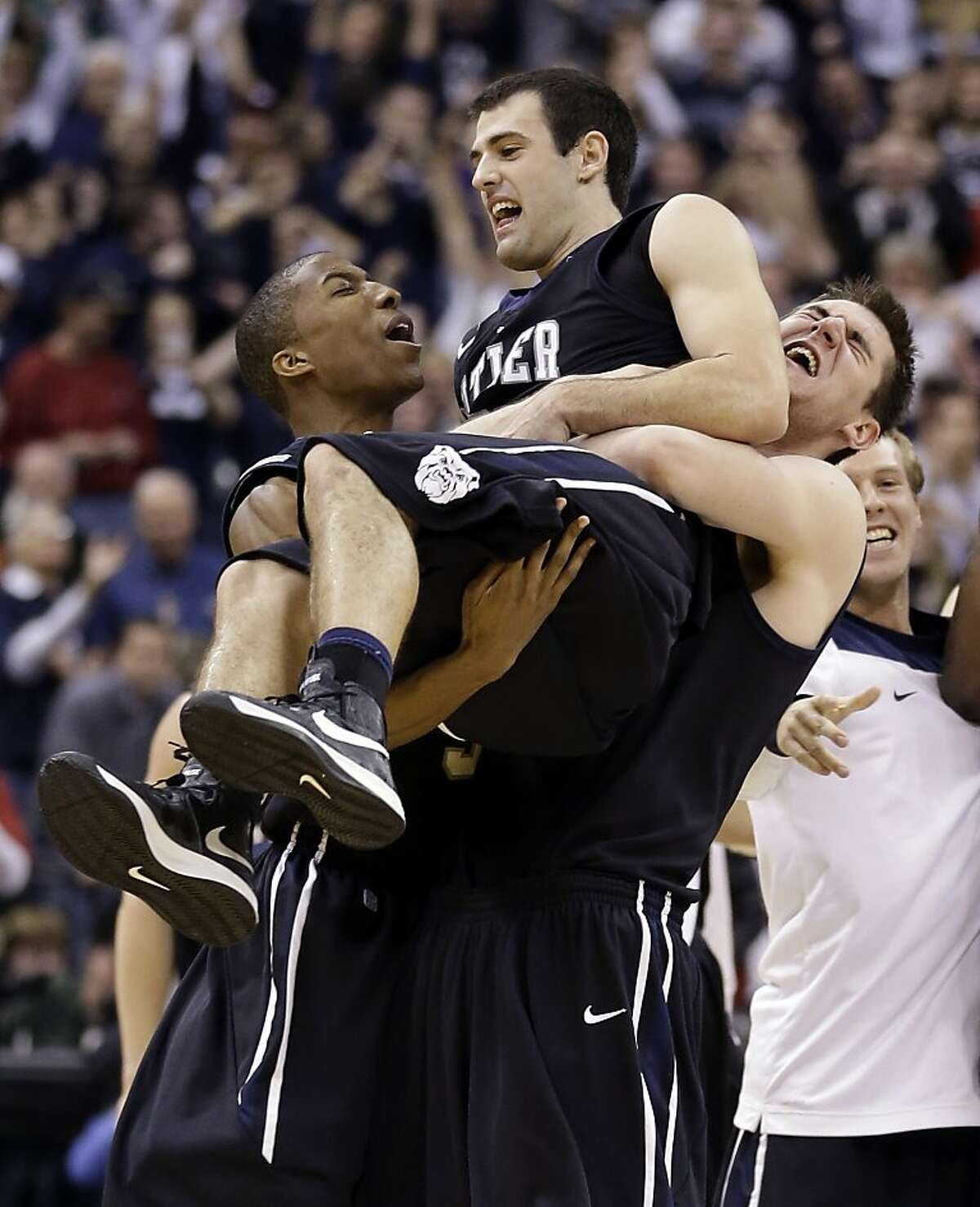 Guard Alex Barlow (center) is carried by teammates after Butler beat No. 1 Indiana 88-86 in overtime in Indianapolis.