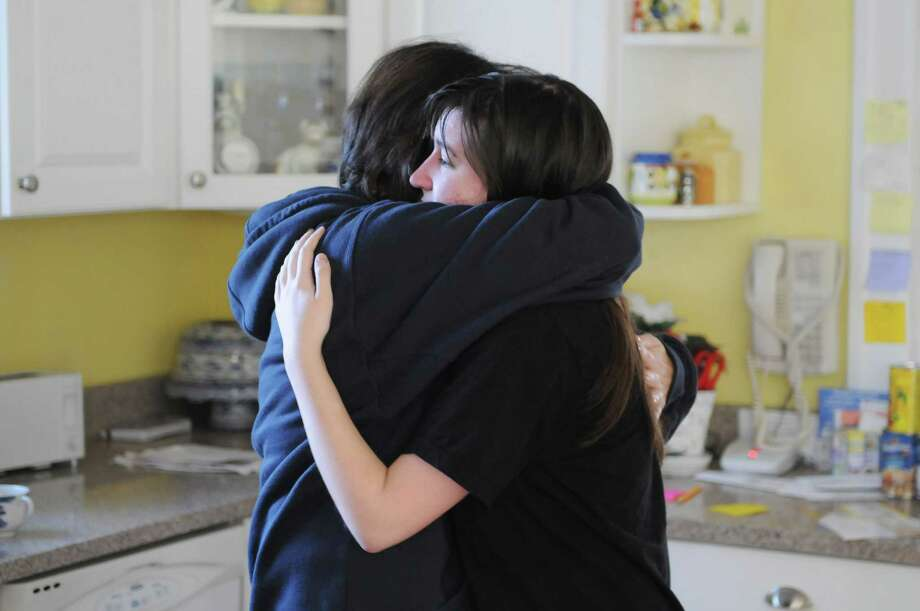 Lois Barber of Newtown, Conn., left, embraces her daughter Lisa in their home, as she became overcome with emotion reflecting on yesterdayâÄôs tragic shooting at Sandy Hook Elementary School, which Lisa once attended. Photo: Will Waldron, Hearst Connecticut Newspapers/Wi / The News-Times