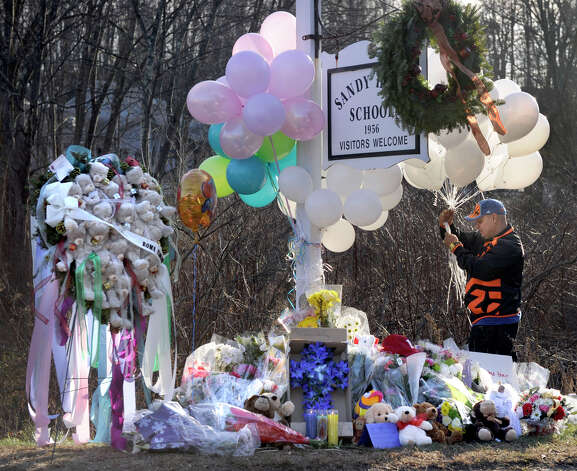 A man places a bunch of balloons to a make-shift memorial at the sign for the Sandy Hook Elementary School in Newtown, Conn. Saturday, Dec. 15, 2012. Photo: Carol Kaliff / The News-Times