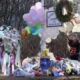 A man places a bunch of balloons to a make-shift memorial at the sign for the Sandy Hook Elementary School in Newtown, Conn. Saturday, Dec. 15, 2012.