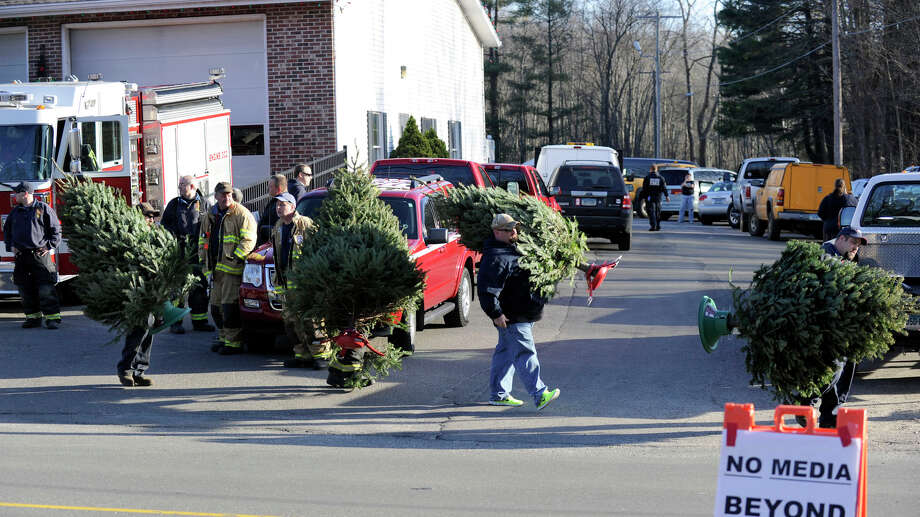 Christmas trees are carried from a near-by firehouse, placed and then decorated along the road leading to the Sandy Hook Elementary School in Newtown, Conn. Saturday, Dec. 15, 2012. Photo: Carol Kaliff / The News-Times