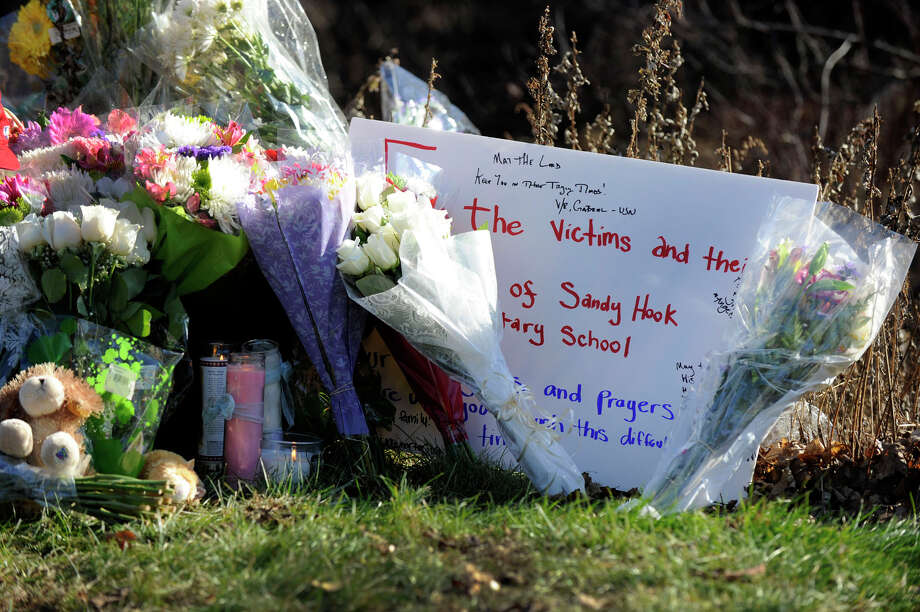 Mourners leave flowers, balloons and notes around the sign for the Sandy Hook Elementary School in Newtown Saturday, Dec. 15, 2012. The day before, a gunman opened fire killing 28 people including himself and 20 children at the school. Photo: Carol Kaliff / The News-Times