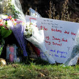 Mourners leave flowers, balloons and notes around the sign for the Sandy Hook Elementary School in Newtown Saturday, Dec. 15, 2012. The day before, a gunman opened fire killing 28 people including himself and 20 children at the school.