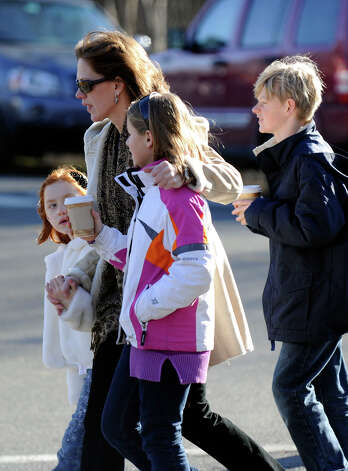 A woman and children pay their respects at a memorial setup at the sign for the Sandy Hook Elementary School Saturday, Dec. 15, 2012 in Newtown, Conn. Photo: Carol Kaliff / The News-Times