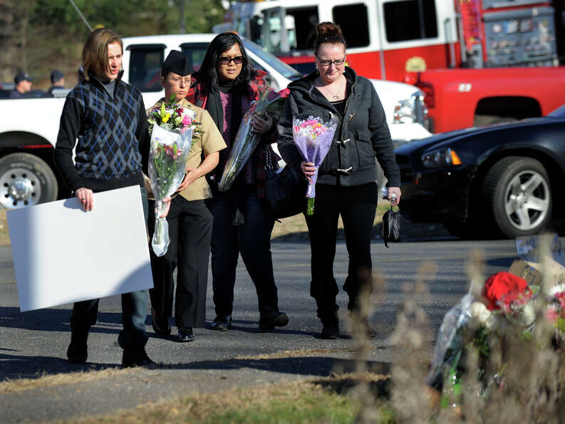Mourners approach a make-shift memorial at the foot of a sign for the Sandy Hook Elementary School i