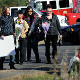 Mourners approach a make-shift memorial at the foot of a sign for the Sandy Hook Elementary School in Newtown, Ct., Saturday afternoon, Dec. 15, 2012.