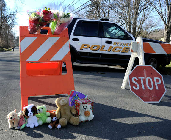 Flowers and stuffed animals are left at a police barrier blocking the way to the Sandy Hook Elementary school in the Sandy Hook section of Newtown, Conn. Saturday, where a gunman opened fire killing 28 people including himself, Friday, Dec. 15, 2012. Photo: Carol Kaliff / The News-Times