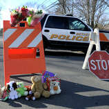 Flowers and stuffed animals are left at a police barrier blocking the way to the Sandy Hook Elementary school in the Sandy Hook section of Newtown, Conn. Saturday, where a gunman opened fire killing 28 people including himself, Friday, Dec. 15, 2012.