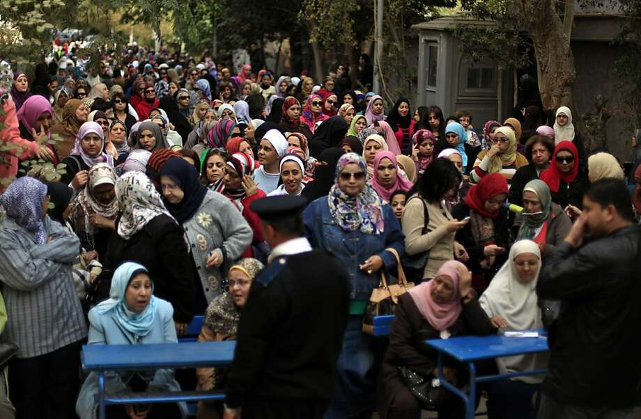 Egyptian women line up outside a polling station to cast their votes during a referendum on a disputed constitution drafted by Islamist supporters of President Morsi in Cairo, Egypt, Saturday, Dec. 15, 2012.(AP Photo/Khalil Hamra) Photo: Khalil Hamra, Associated Press