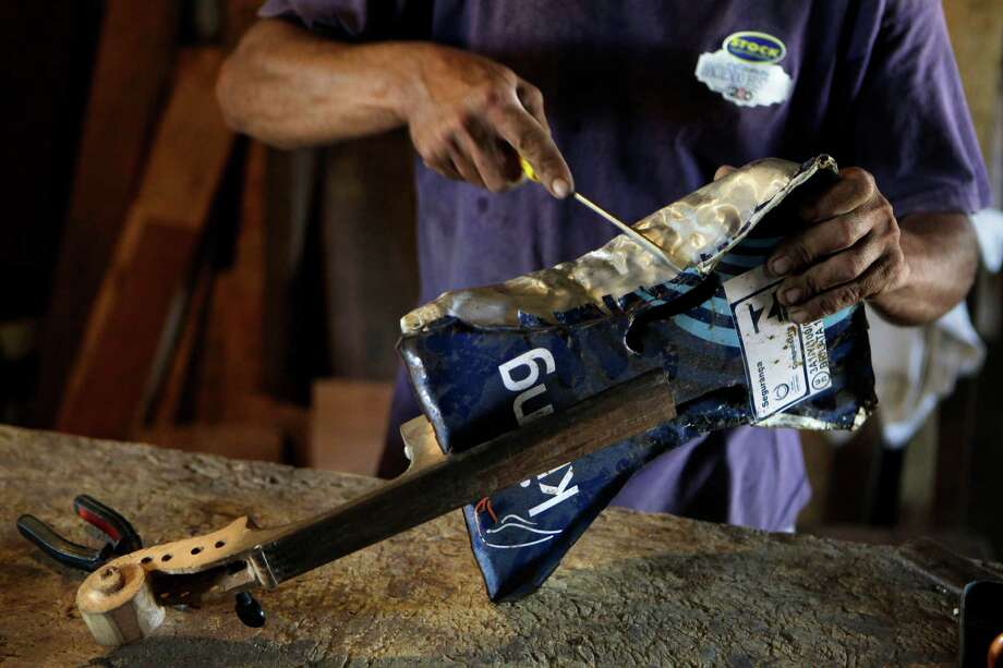 Nicolas Gomez makes a violin with recycled materials at his home in the Cateura, a vast landfill outside Paraguay's capital of Asuncion. Photo: Jorge Saenz, STF / AP