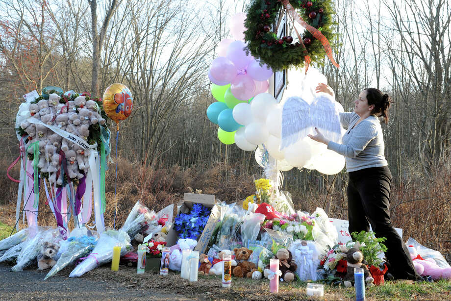 Judith DeLisa, of Shelton, hangs a pair of angels wings on the sign in front of Sandy Hook Elementary School, in Newtown, Conn., Dec. 15th, 2012. The sign has become a memorial to those killed at the school on Friday. Photo: Ned Gerard / Connecticut Post