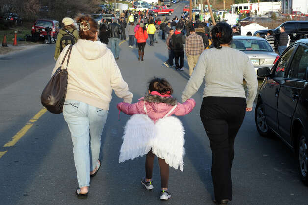 Wearing a pair a angel's wings, 5-year Calliope CeBallos, of Shelton, walks with her family towards Sandy Hook Elementary School, in Newtown, Conn., Dec. 15th, 2012. They left the wings on the school's sign, which has become a memorial to those killed at the school on Friday. Photo: Ned Gerard / Connecticut Post