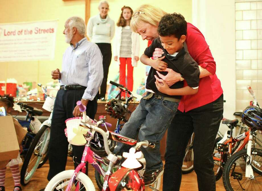 Leiselle Sadler, of Trinity Episcopal Church, helps Justin Tejeda, 4, get on his new bike at the Lord of the Streets party. Photo: Nick De La Torre, Staff / © 2012  Houston Chronicle