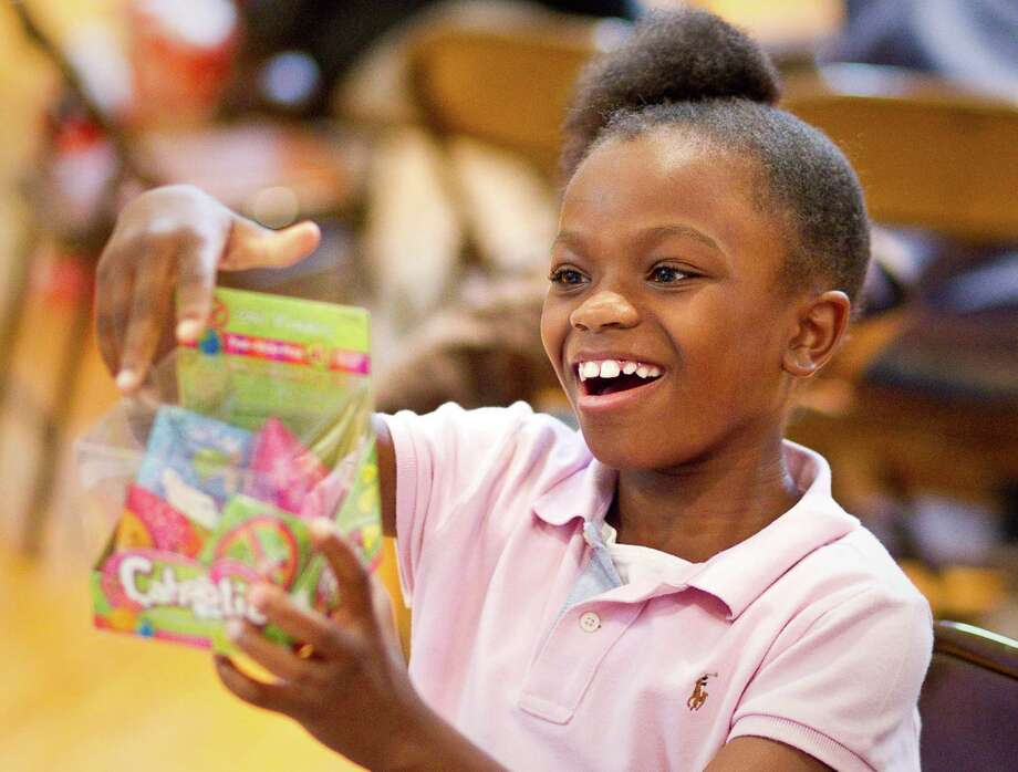 Autumn Roberts, 9, smiles at the gift she received after she was allowed to open one present during the Lord of the Streets 'Angel Tree' Christmas party. Photo: Nick De La Torre, Houston Chronicle / © 2012  Houston Chronicle