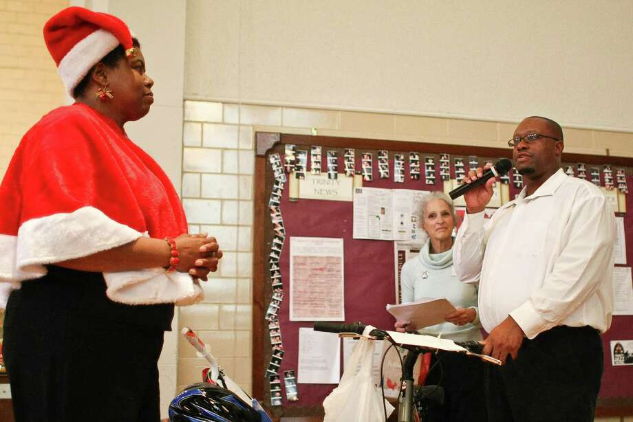 Damion Waker, right says a few words after accepting presents during the Lord of the Streets 'Angel Tree' Christmas party. Mayra Mitchell, volunteer coordinator for Lord of the Streets, left, and Laura Daughtrey, stood with Waker. Photo: Nick De La Torre, Houston Chronicle / © 2012  Houston Chronicle
