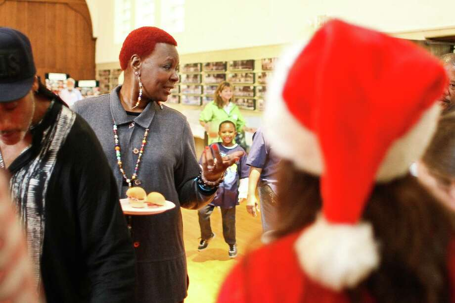 Eunice Dewhart, of Houston, visits with friends as she waits in line for lunch as during the Lord of the Streets 'Angel Tree' Christmas party, Saturday, Dec. 15, 2012, at Trinity Episcopal Church in Houston. Photo: Nick De La Torre, Houston Chronicle / © 2012  Houston Chronicle
