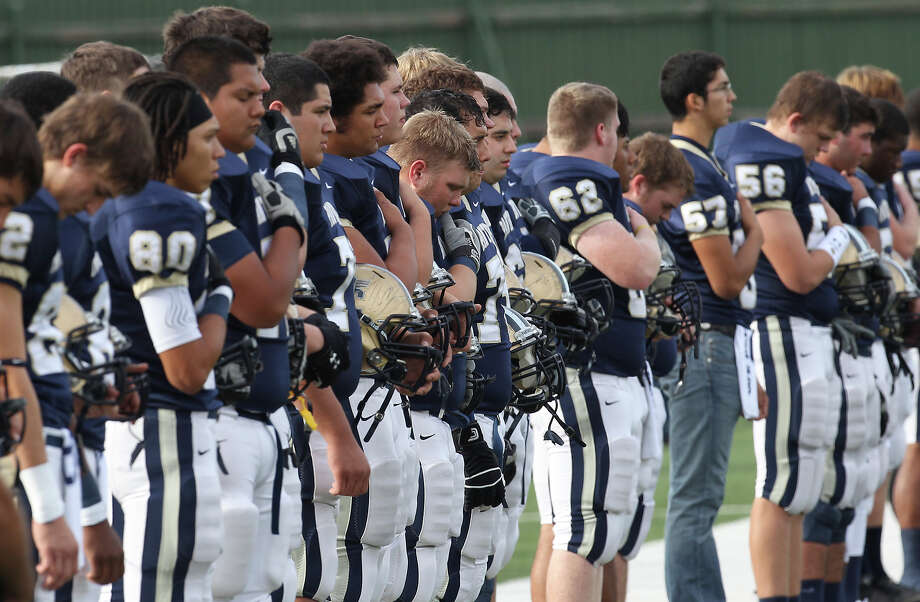 O'Connor players take a moment of silence to honor the victims in the Connecticut elementary school shootings before their game against Houston Lamar in the Class 5A Div. I state semifinal football game in Austin on Saturday, Dec. 15, 2012. O'Connor lost to Lamar, 15-7. Photo: Kin Man Hui, Express-News / © 2012 San Antonio Express-News