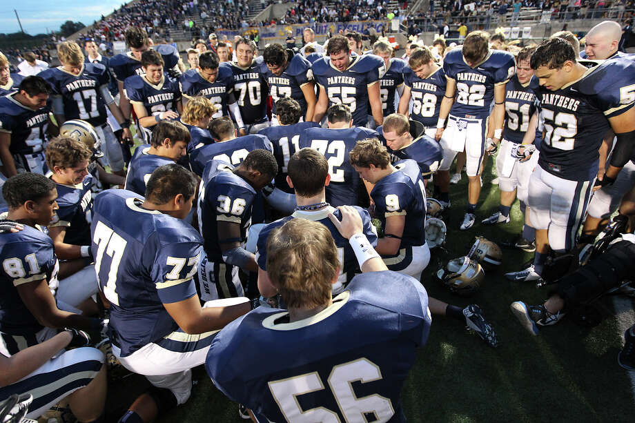 O'Connor players gather to pray at the end of their game against Houston Lamar in the Class 5A Div. I state semifinal football game in Austin on Saturday, Dec. 15, 2012. O'Connor lost to Lamar, 15-7. Photo: Kin Man Hui, Express-News / © 2012 San Antonio Express-News