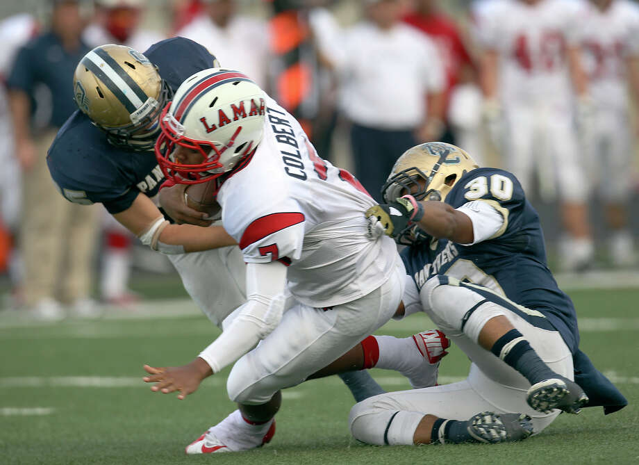 O'Connor's Luke Farmer (left) and Marces Garza-Dishmon (30) make a tackle on Houston Lamar quarterback Darrell Colbert (07) in the first half in the Class 5A Div. I state semifinal football game in Austin on Saturday, Dec. 15, 2012. O'Connor lost to Lamar, 15-7. Photo: Kin Man Hui, Express-News / © 2012 San Antonio Express-News