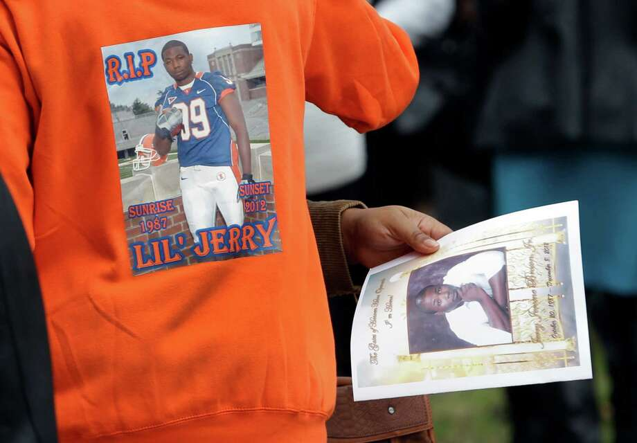 A man wears a shirt with a picture of Jerry Brown, a linebacker on the Dallas Cowboys practice squad, as another person holds a program for Brown's funeral service outside Hopewell Missionary Baptist Church Saturday, Dec. 15, 2012, in St. Louis. Brown was killed in a car accident on Dec. 8, that left his teammate and friend, Cowboys defensive tackle Josh Brent, facing a manslaughter charge for allegedly driving drunk. (AP Photo/Jeff Roberson) Photo: Jeff Roberson, Associated Press / AP