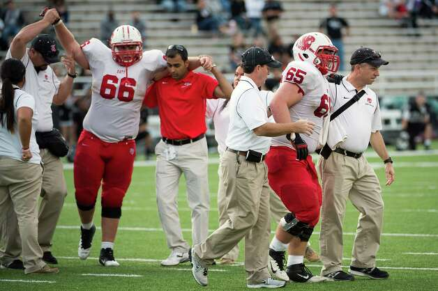 Katy offensive linemen John Kellogg (66) and Kyle Miller (65) are helped off the field after being injured on the same play during the fourth quarter against the Cibolo Steele in a Class 5A Division II state high school football semifinal game at Floyd Casey Stadium on Saturday, Dec. 15, 2012, in Waco.  Katy won the game 45-33. (Smiley N. Pool / Houston Chronicle ) Photo: Smiley N. Pool, Express-News / © 2012  Houston Chronicle