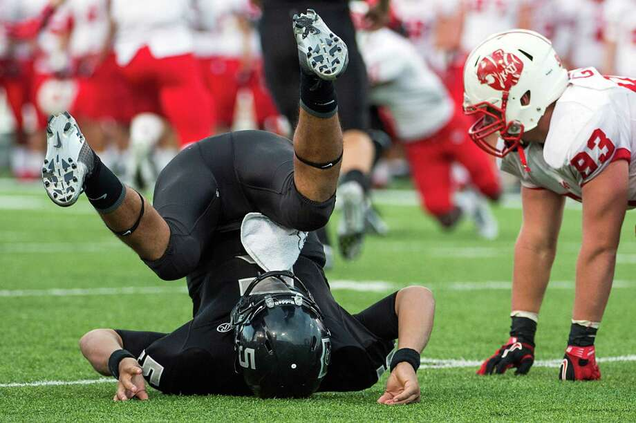 Cibolo Steele quarterback Breylann McCollum (5) takes a tumble after a hit from Katy defensive lineman Cody Gessler (93) during the fourth quarter in a Class 5A Division II state high school football semifinal game at Floyd Casey Stadium on Saturday, Dec. 15, 2012, in Waco.  Katy won the game 45-33. (Smiley N. Pool / Houston Chronicle ) Photo: Smiley N. Pool, Express-News / © 2012  Houston Chronicle