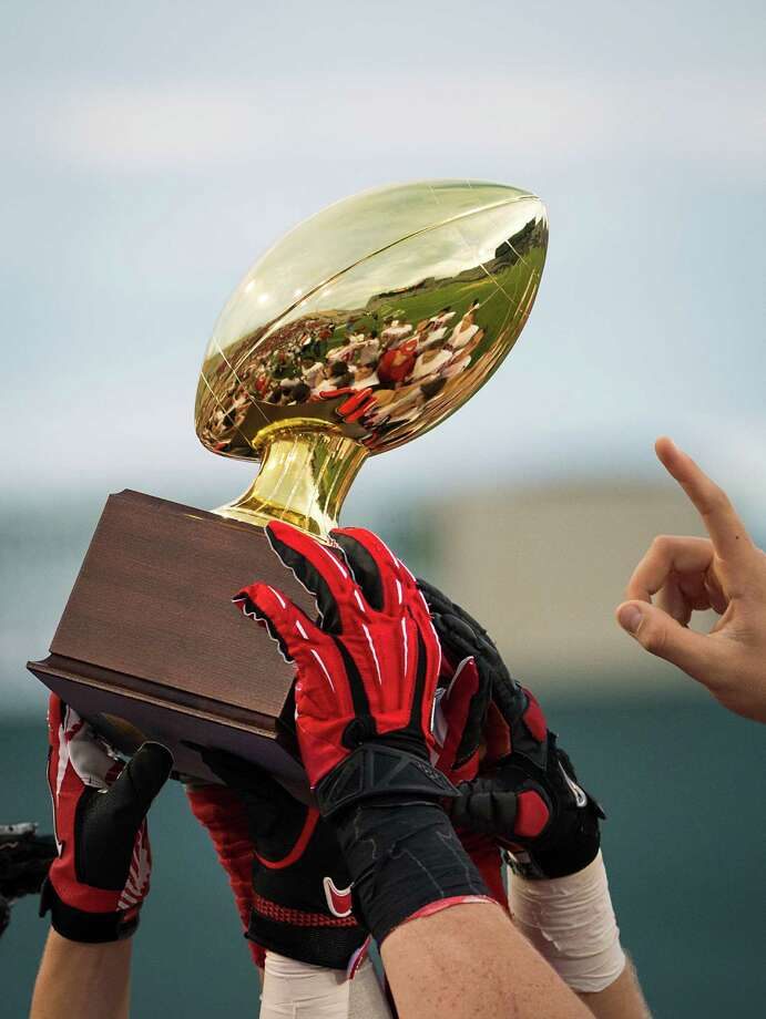 Katy players reach for the Class 5A Division II state semifinal champions trophy after the Tigers victory over Cibolo Steele in a high school football playoff game at Floyd Casey Stadium on Saturday, Dec. 15, 2012, in Waco.  Katy won the game 45-33. (Smiley N. Pool / Houston Chronicle ) Photo: Smiley N. Pool, Express-News / © 2012  Houston Chronicle
