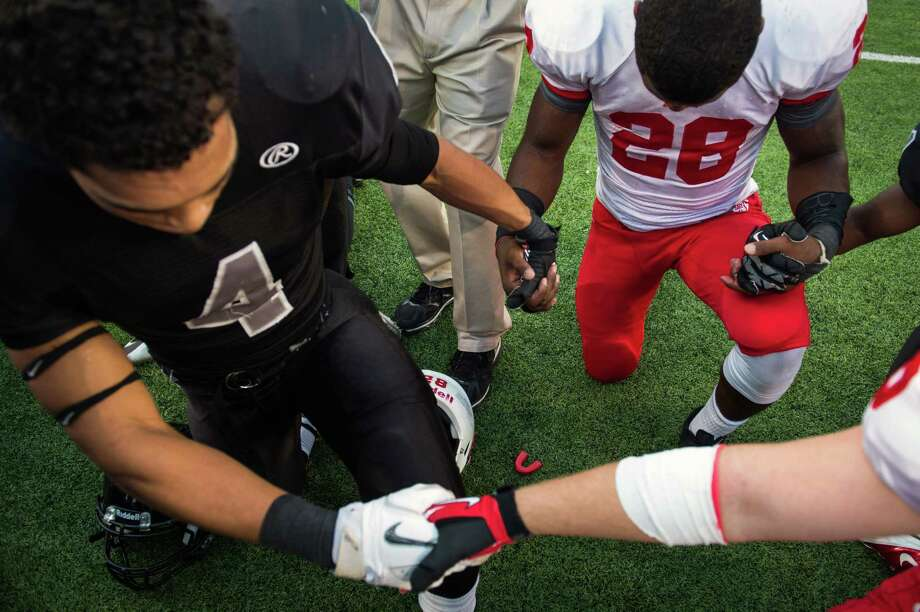 Katy running back Adam Taylor (28) joins hands in payer with Cibolo Steele running back Justin Stockton (4) following a Class 5A Division II state high school football semifinal game at Floyd Casey Stadium on Saturday, Dec. 15, 2012, in Waco.  Katy won the game 45-33. (Smiley N. Pool / Houston Chronicle ) Photo: Smiley N. Pool, Express-News / © 2012  Houston Chronicle