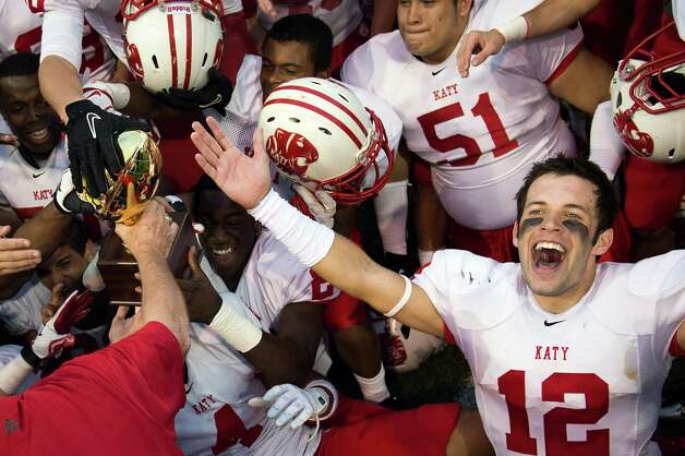 Katy wide receiver Andrew Englett (12) celebrates with his teammates as they reach for the Class 5A Division II state semifinal champions trophy after the Tigers victory over Cibolo Steele in a high school football playoff game at Floyd Casey Stadium on Saturday, Dec. 15, 2012, in Waco.  Katy won the game 45-33. (Smiley N. Pool / Houston Chronicle ) Photo: Smiley N. Pool, Express-News / © 2012  Houston Chronicle