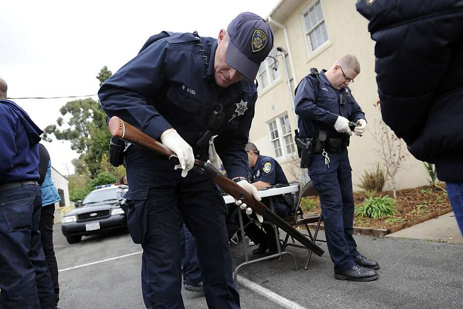 Officers Richard Niven (left) and Jeffrey Smoak handle guns that were bought back at St. Benedict's Church in Oakland. Photo: Michael Short, Special To The Chronicle