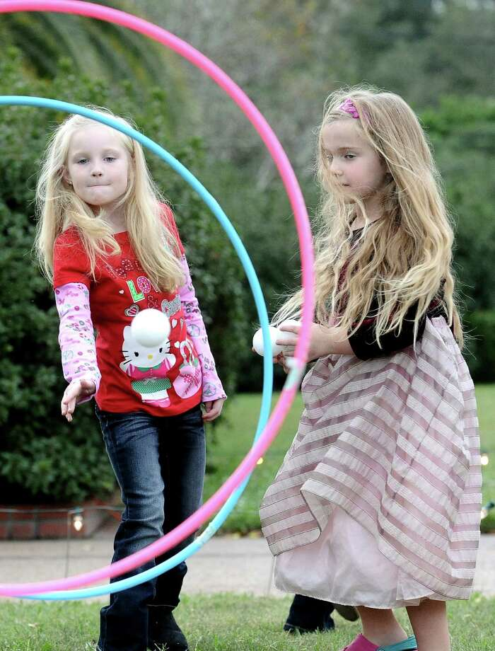 From left to right, Andie Brammer, 6, and Virginia Wood, 5, throw snowballs through hoops held by volunteers at the McFaddin-Ward Christmas Open House on Saturday, December 15, 2012 at the McFaddin-Ward House. Photo taken: Randy Edwards/The Enterprise Photo: Randy Edwards